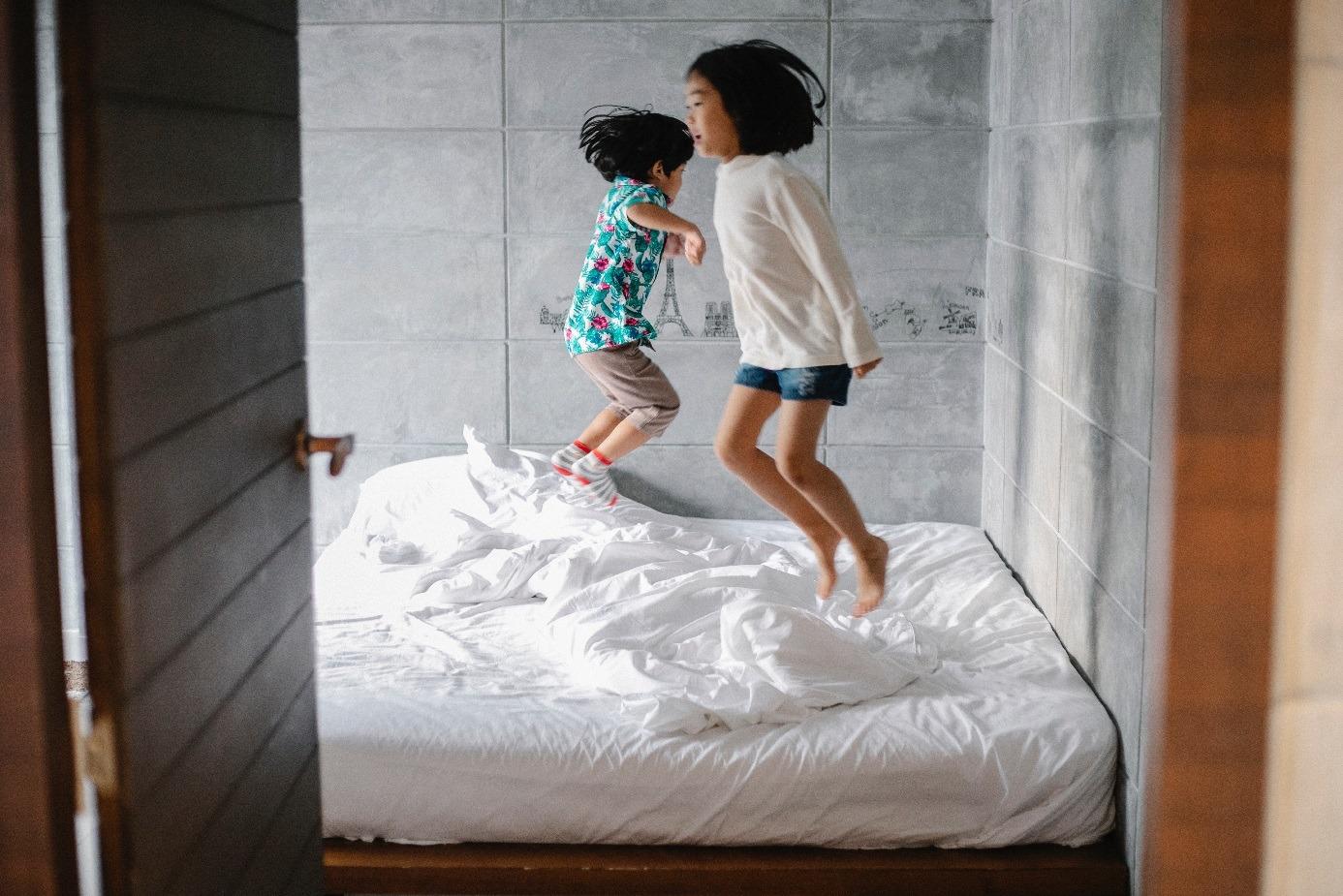 Deus enfants qui sautent sur un lit